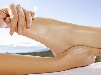 Woman legs get foot massage with blue sky background. This is spa concept
